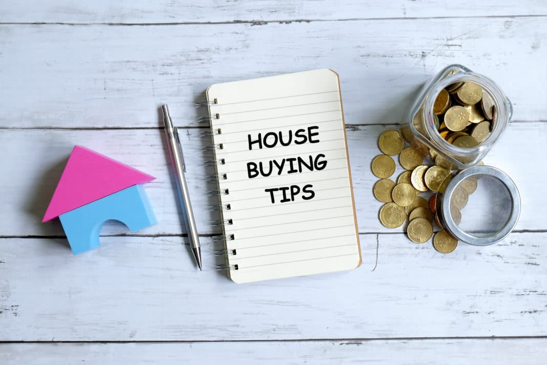 Notebook on a desk that reads Home Buying Tips next to a penny jar